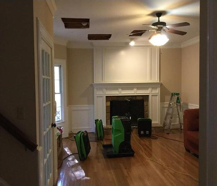 Restoration of hardwood floors with green SERVPRO equipment in place